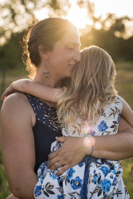 Denver outdoor family photo shoot, mom snuggles with little girl in stunning Colorado sunset
