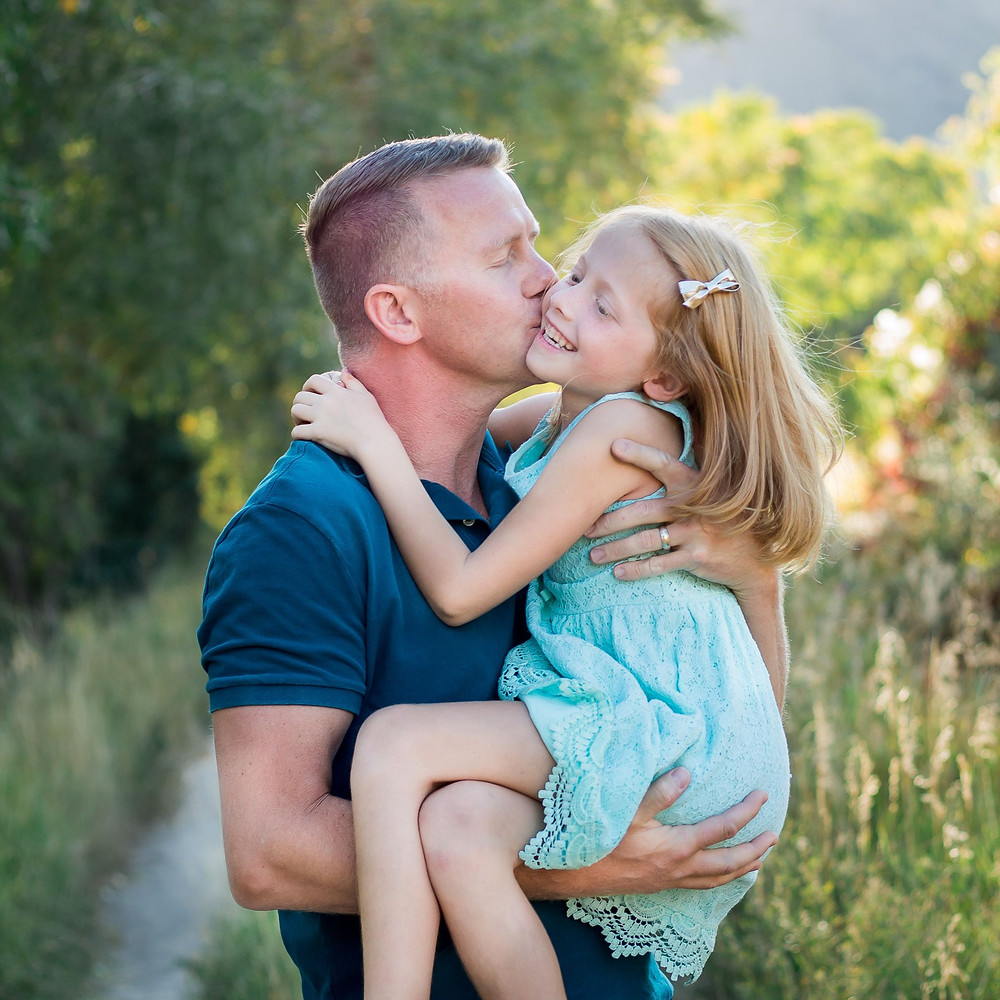 Daddy snuggles little girl in fall sunset lighting