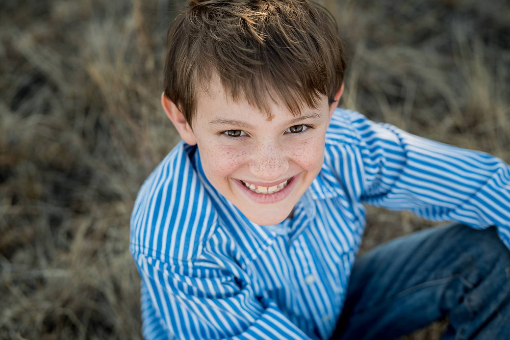 Boy smiles up at camera in a Colorado Family Portrait session.