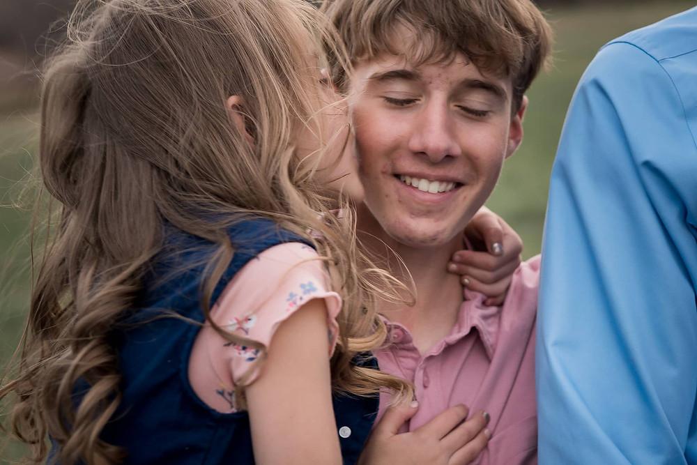 Sister kisses brother in a Denver area portrait session
