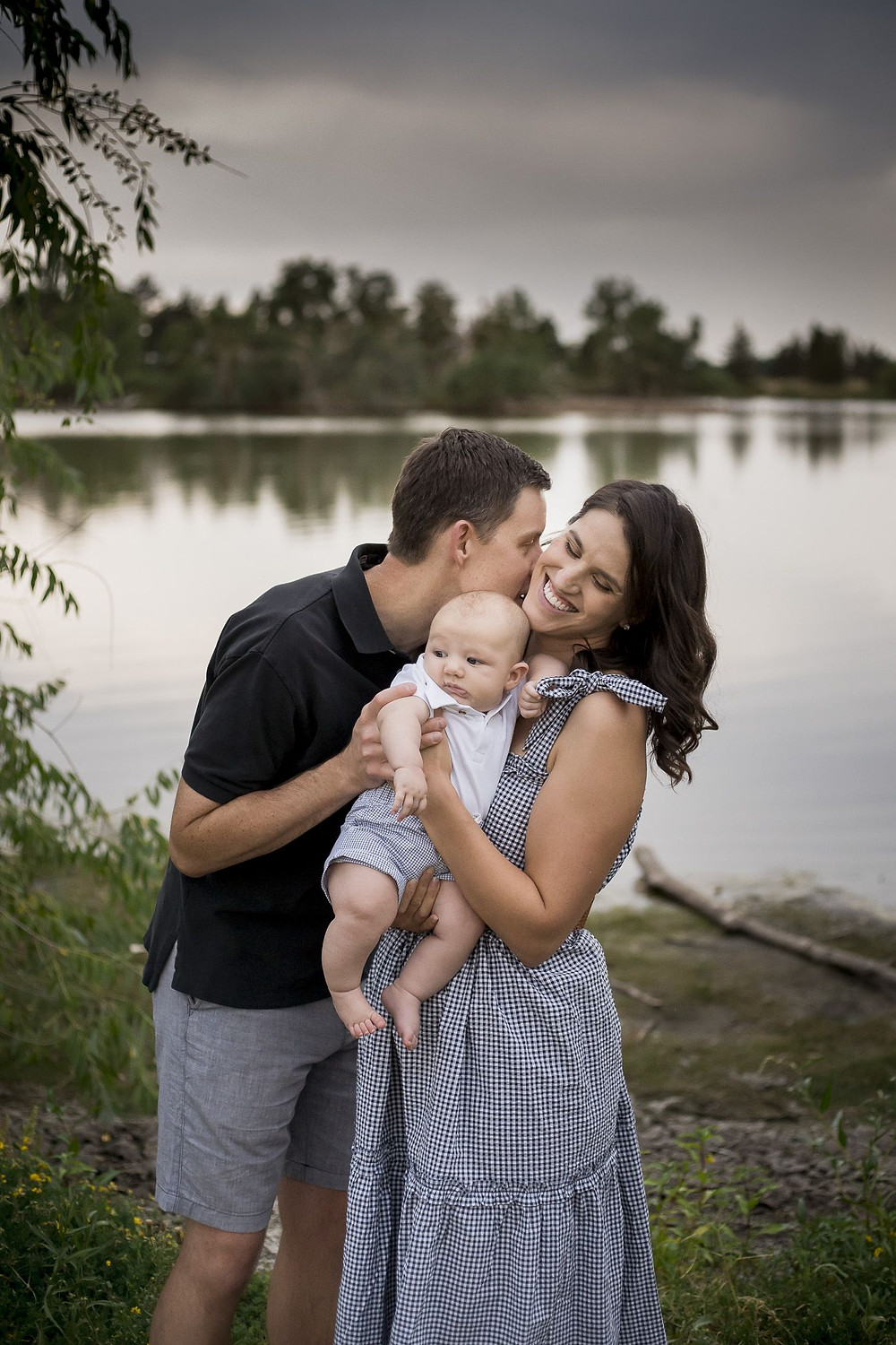 Husband and wife with baby under cloudy sky