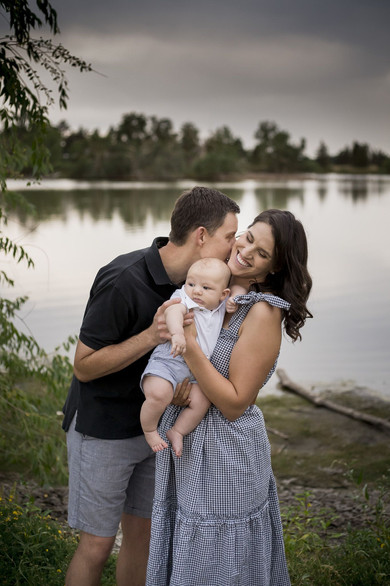 Denver outdoor family photo shoot, dad snuggles into mom's neck
