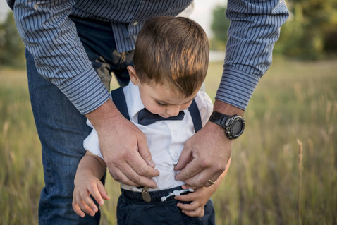 Outdoor family photo shoot, dad helps son with buttons