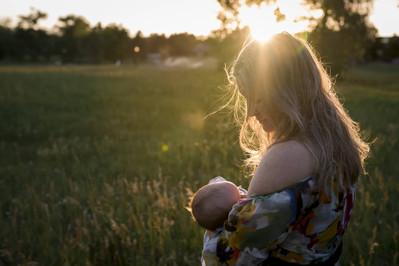 Outdoor family photo shoot, mom nurses in sunset