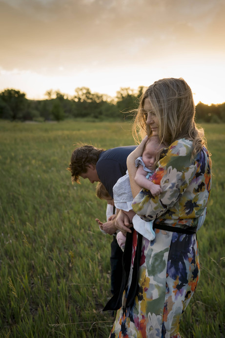 Outdoor family photo shoot, mom snuggles newborn close while dad attends to son