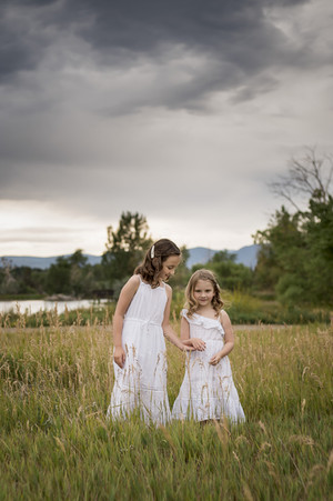 Denver outdoor family photo shoot, sisters hold hands with dramatic clouds as background