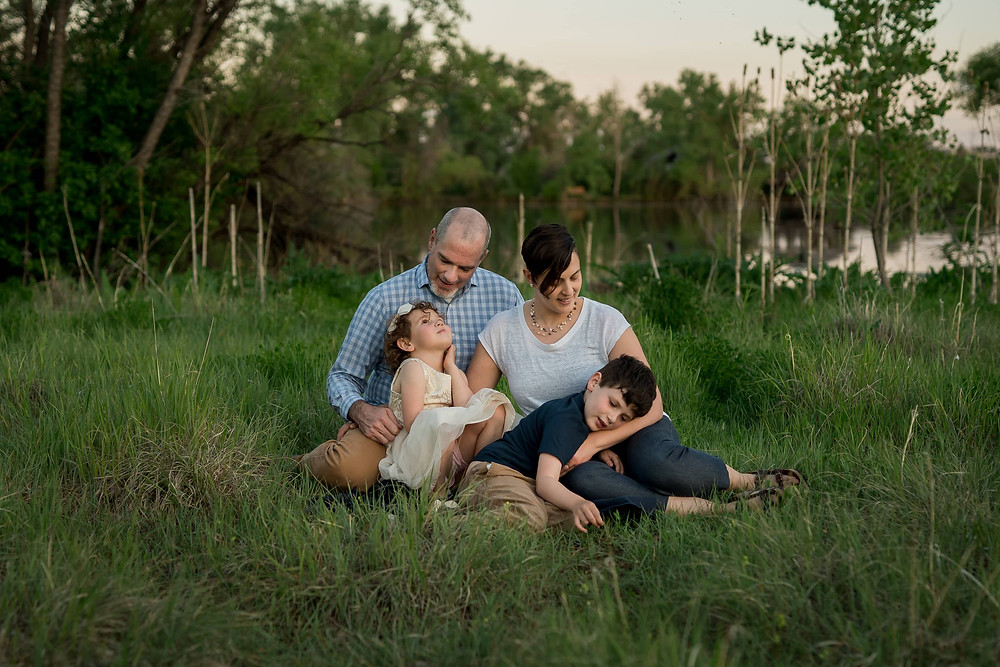 Family snuggles in grass, lifestyle family portrait Lakewood, Colorado
