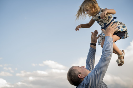 Outdoor family photo shoot, dad throws little girl into the air with clouds in background