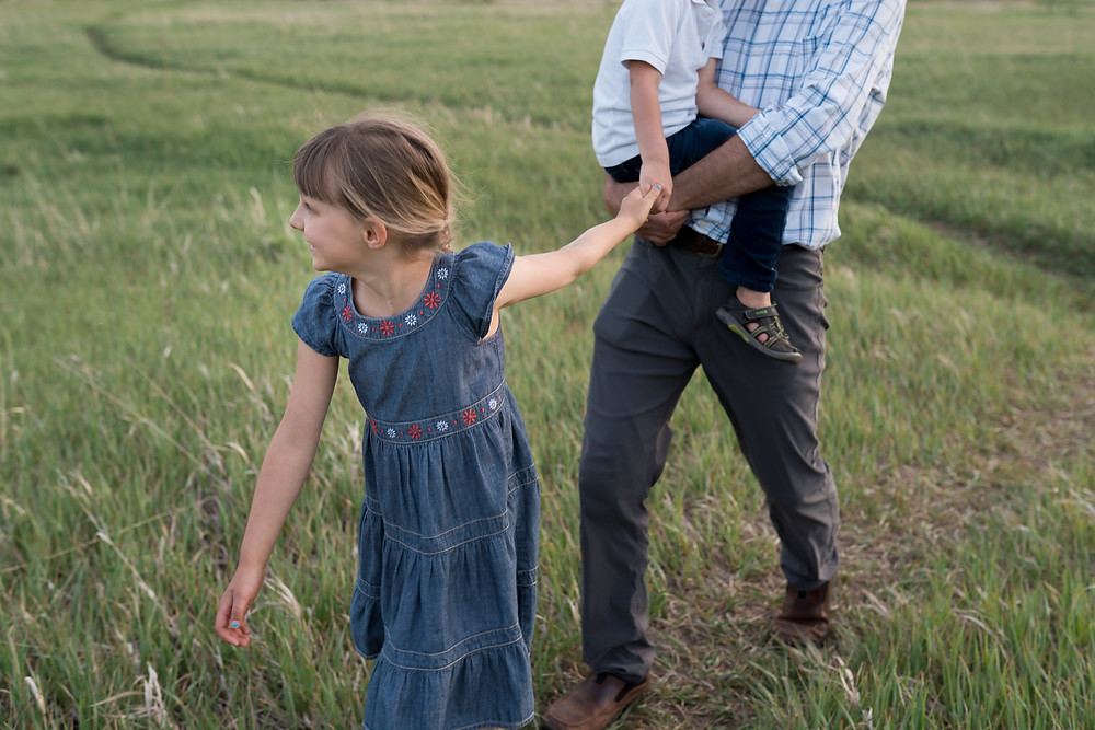 Girl leading father through field Lakewood, Colorado