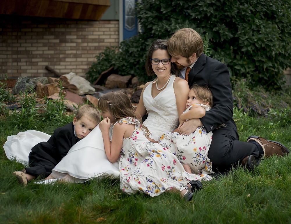 Family photographer Holly Freeman captures image of husband and wife celebrating anniversary in wedding attire with children snuggled around them in Arvada, Colorado