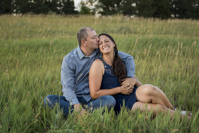 Outdoor family photo shoot, dad kisses mom, snuggled in grass