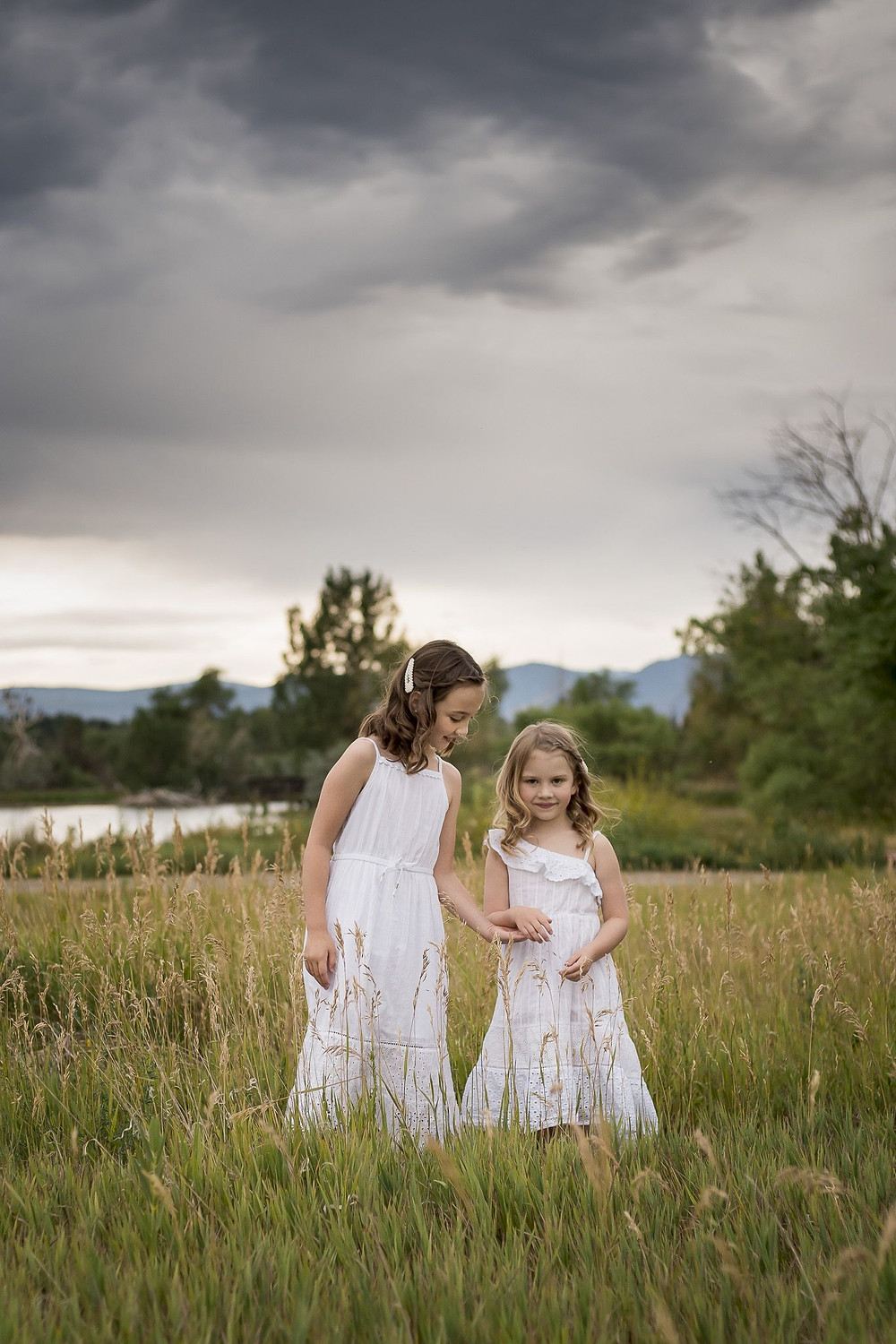 Sisters hold hands under cloudy sky, Lakewood, Colorado