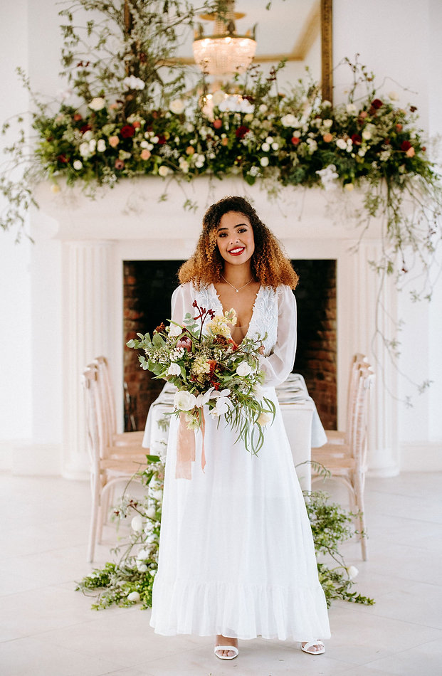 A Bride with bouquet in front of a dressed mantel.