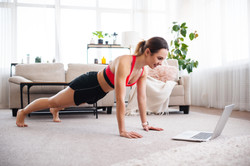 Fitness woman using online platform to exercise at home