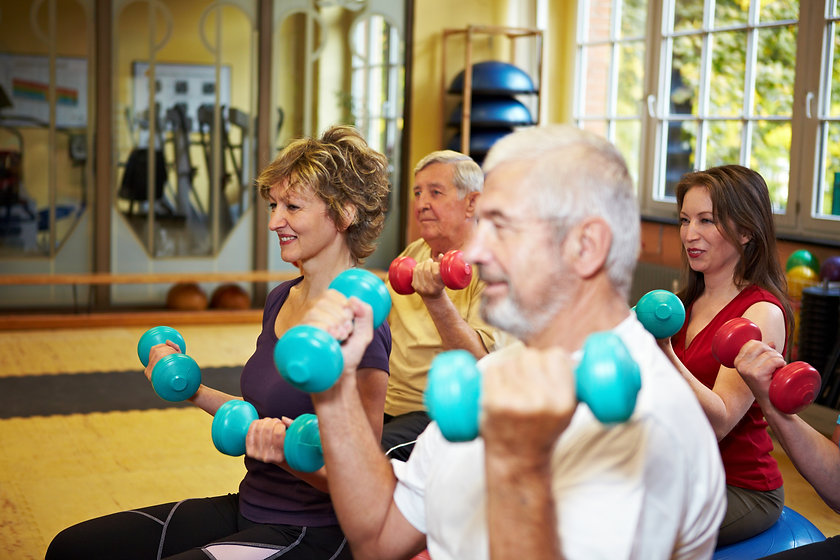 Mixed group doing dumbbell exercises in