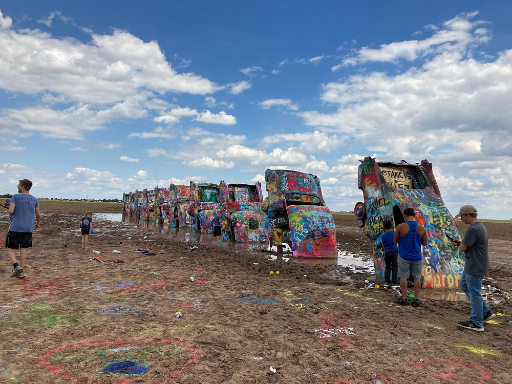 people spray painting the Cadillac Ranch