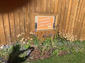"""bed of flowers under """"A Library Champion Lives Here"""" sign"""