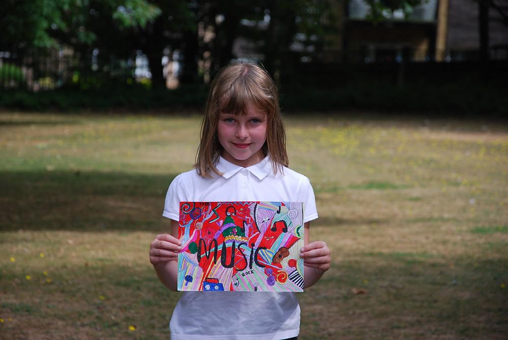 Holly Barham, age 9, with her winning artwork.