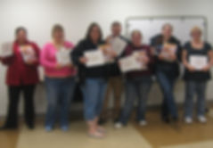Happy graduates, showing off their certificates of achievement