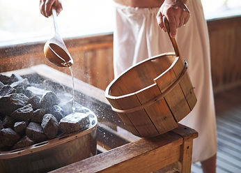 Man pouring water onto hot stone in sauna room. Steam on the stones, spa and wellness conc