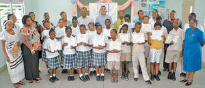 Joel Primus, back row, fifth from left, community sustainability and stakeholder relations adviser, bpTT; and Christopher Bonterre, back row, centre, director, Arrow Foundation, share a proud moment with the top performing students and teachers of Carenage Boys' and Carenage Girls' Primary Schools at the graduation.