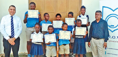Students of Woodbrook Presbyterian Primary School proudly show off their certificates having successfully completed computer-based literacy training delivered by the Arrow Foundation. Sharing in the special moment are Christopher Bonterre (left), Arrow Foundation managing director and acting principal of the school, Terrence Choutie.