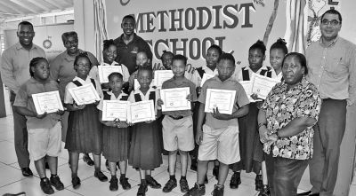 Joel Primus, left, Community Sustainability and Stakeholder Relations Adviser, bpTT; Christopher Bonterre, right, Director, Arrow Foundation; and Arrow trainer, Stephen Joseph, back row, third from left, share a proud moment with the top performing students and Arrow trained teachers of Charlotteville Methodist Primary School