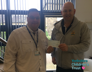 Richard from Halifax RLFC with a cheque from Calderdale Cares Lottery - CashFAX