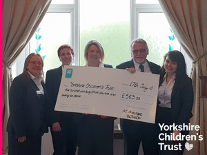 Kevin Mitchell and Coop Funeral Care holding up a cheque for Yorkshire Children's Trust, a local charity, helping local children.