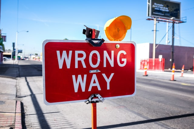 """Red and white """"wrong way"""" sign with amber light fixed to the top right corner"""