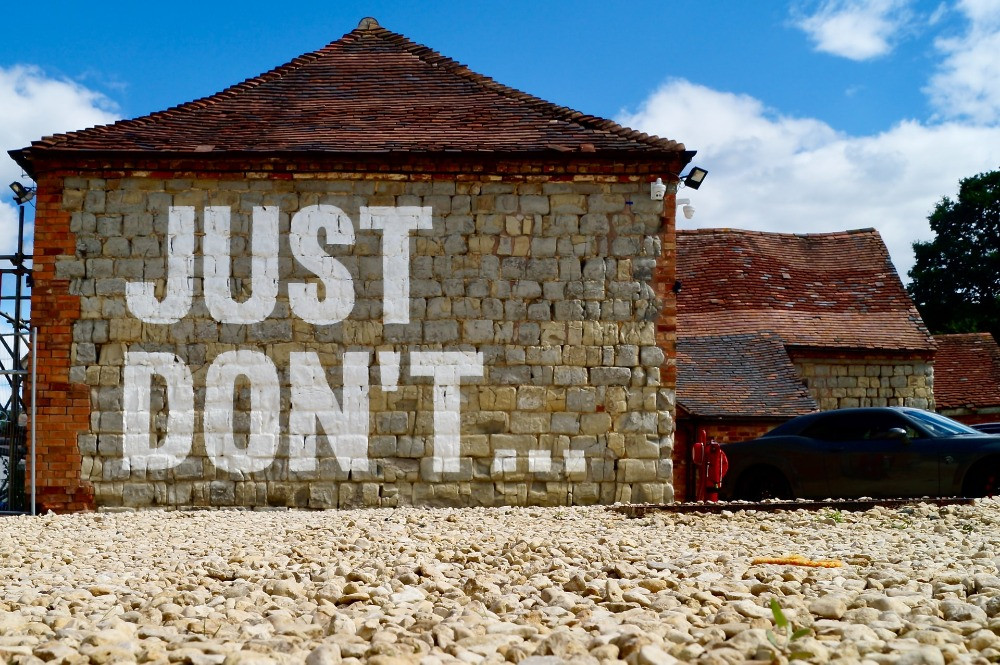 """A brick building with a red tiled roof, and the words """"Just Don't"""" painted in large letters on the wall. Image source: James Orr on Unsplash"""