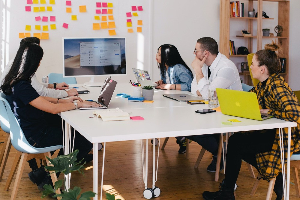 Group of people sat around a white table, looking at a computer screen surrounded by neon coloured post-it notes on the wall