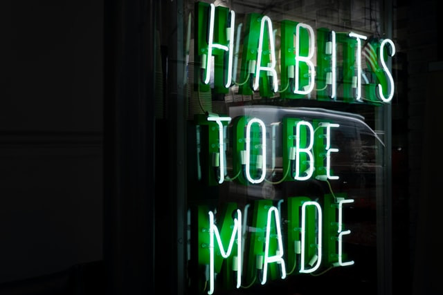 """Neon green sign with the words """"Habits to be made"""". Photo by Drew Beamer on Unsplash"""