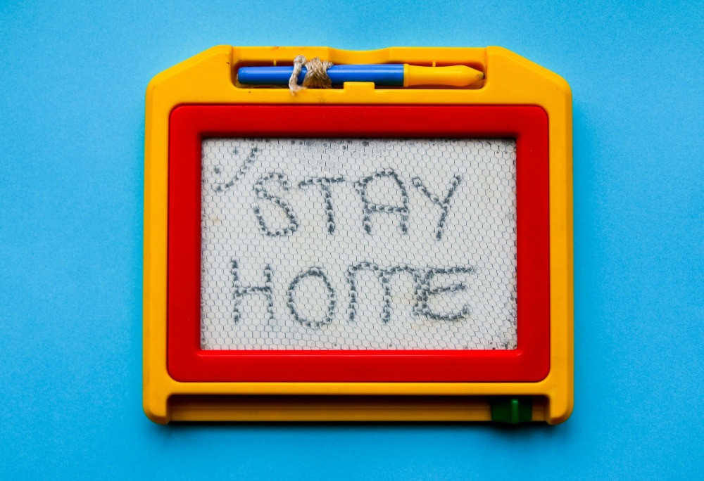 Red and yellow board with the words 'stay home' written on it. Photo by Glen Carrie on Unsplash