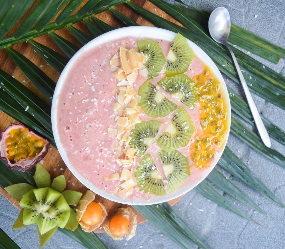 Morning smoothie bowl with a tropical twist - hello YUM! Banana & pineapple blended deliciousness with extra added nutritional benefits from the Maca and beetroot powder. This fun, pink, plant-based smoothie bowl is sure to keep you feeling full throughout your busy mornings! Easily transfer your smoothie into a cup for a grab-and-go breakfast option that doesn't sacrifice your health. It's filling, fresh, tropical bliss in a cup!