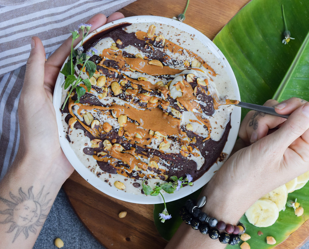 Chocolate with breakfast! Try out this 'snickers' plant-based smoothie bowl! I use whole, real and fresh ingredients for added health benefits and easy digestion! A banana and coconut milk blend topped with nut butter, peanuts, coconut shreds, and a chocolate drizzle. This vegan and gluten-free breakfast recipe will leave you full, and smiling ear to ear!