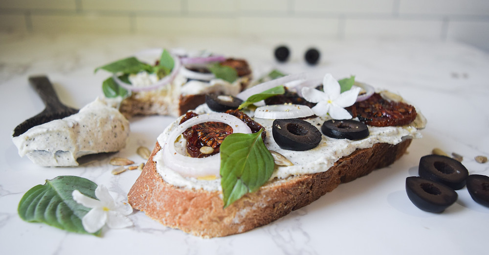 This loaded toast is a plant-based meal that can be created in so many delicious ways! Use ingredients you have on hand, smear on what you love, leave off ingredients you don't like... boost your own culinary confidence! It's a 10 minute meal that satisfies for a quick breakfast, snack, or main meal. This creation uses wholesome vegan cream-cheese, sun-dried tomatoes, olives, onions, sunflower seeds, fresh herbs and spices! Opt for gluten-free bread or a homemade loaf with clean and minimal ingredients!