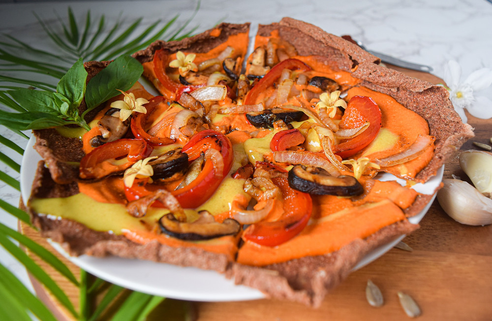 This healthy, vegan, gluten-free pizza recipe is sure to WOW all pizza lovers of any age! The pizza crust is a raw dehydrated base. The pizza sauce is a roasted red pepper and cashew blend. What's pizza without cheese? This vegan cheese recipe is simple, easy and goes delicious on top of your plant-based pizza! Add some sautéed veggies for toppings and you've created an amazing pizza master piece! Grab a slice before it's all gone...