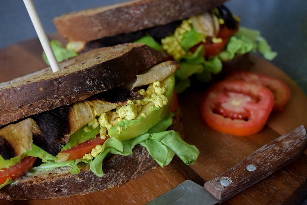 Rise and shine! Start the day with this vegan 'bacon', 'egg' and veggie sandwich recipe! Marinated white Daikon radish for the crispy 'bacon', easy and quick 'eggy' tofu, and of course topped with avocado, lettuce and tomato to make this a hearty and filling breakfast choice. Vegan comfort food for a joyous morning!