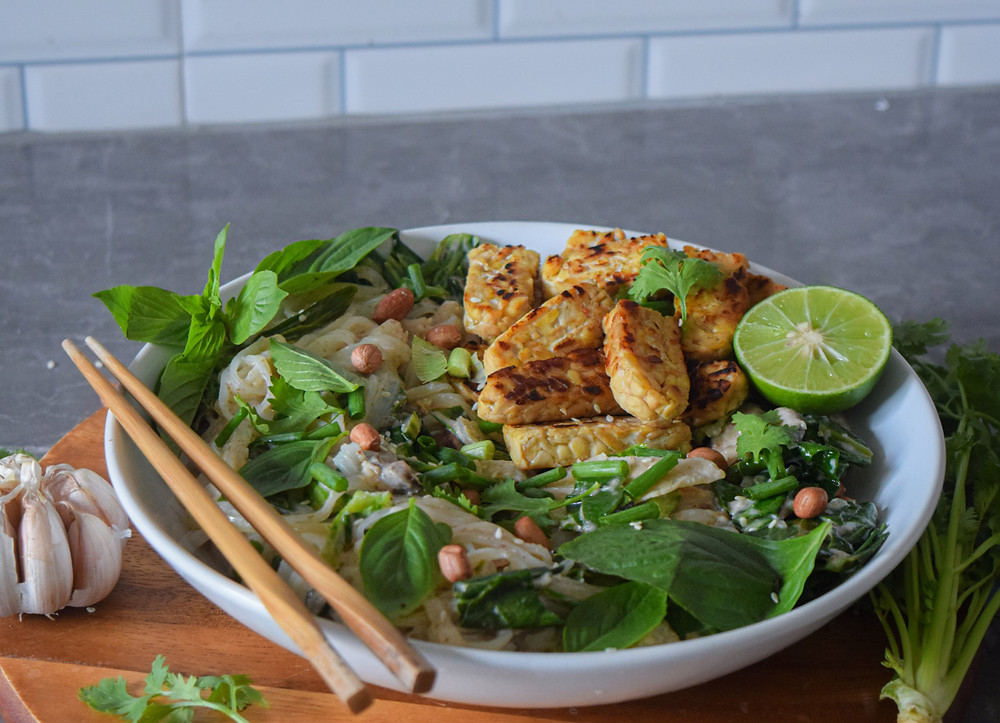 This plant-based, Thai inspired dish is sure to satisfy! My recipe takes just 30 minutes and supports a  healthy, vegan, and gluten-free diet. Rice noodles and marinated tempeh simmered in a peanut sauce - YUM! It will leave you feeling full without the additional bloat. It's convenience and quick prep is just an added bonus to the bold flavor combination!