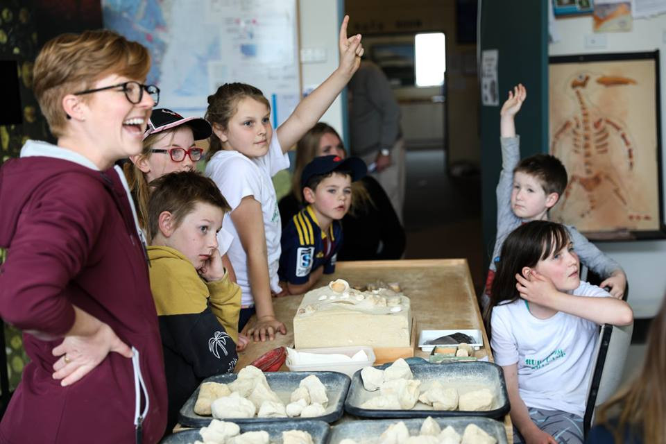 Kids learning about fossils and limestone with teacher