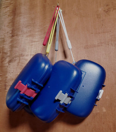 Four Portineer Carry-Dri EZ travel soap containers hanging from lanyards