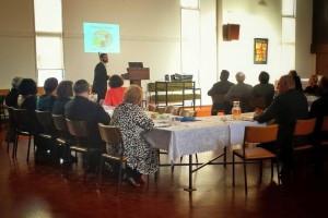 Rabbi Mizrahi explaining the seder plate to attendees.