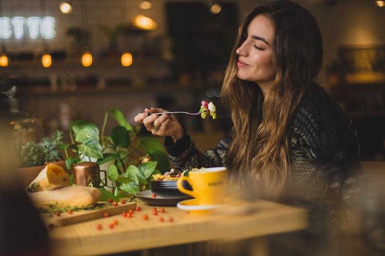 Jua herbs woman smiling in a lowlit restaurant eating healthy food
