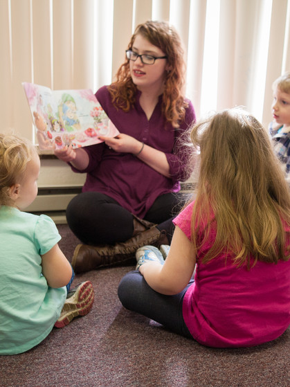Chessie Hatfield reading a book during story hour.