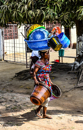A woman balances plastic containers on her head as she goes to sell them in a nearby market.