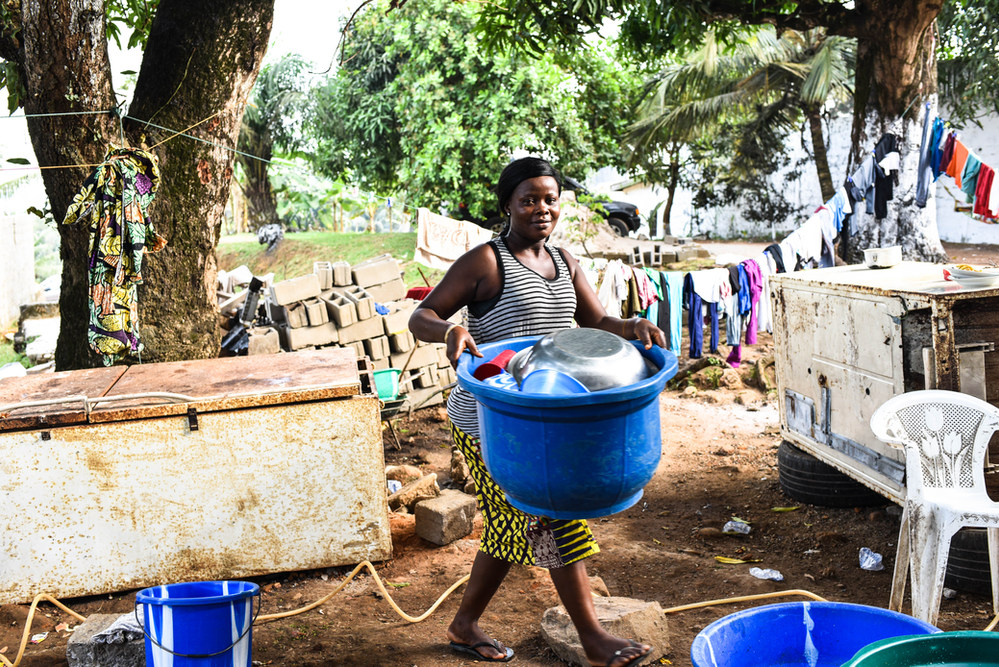 A young woman doing dishes and laundry in the yard of the home where she works