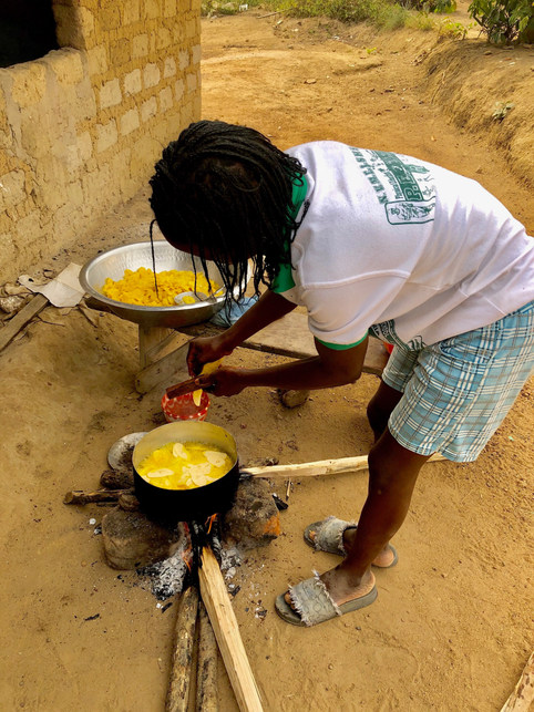 A young woman makes plantain chips by the side of the road in Margibi. She will sell these by the bag to make extra money for her family.