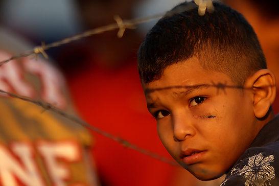 Brayan Enamorado, de 11 años, años observa un pelotón de policías antimotines que esperaban la orden para desalojar unas 200 familias de un predio denominado Rancho El Coco en San Pedro Sula, al norte de la capital, en donde él vive con sus padres y una hermana de tres años. La propiedad de dicho terreo es reclamada por la Universidad Nacional Autónoma de Honduras.