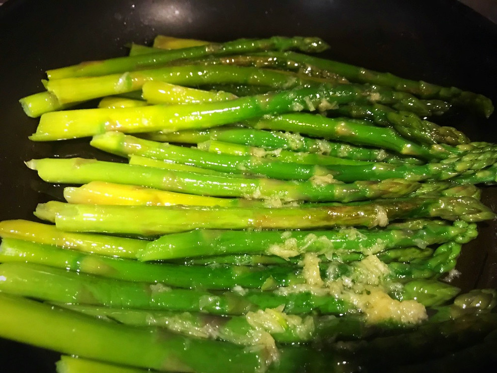 Sautéing asparagus and adding garlic